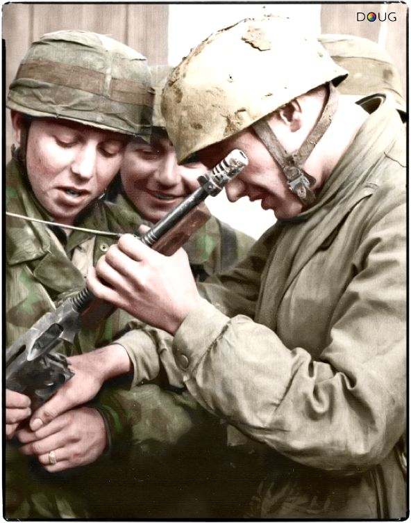 A group of Fallschirmjäger (German paratroopers) are examining a captured M1928A1 Thompson ..jpg