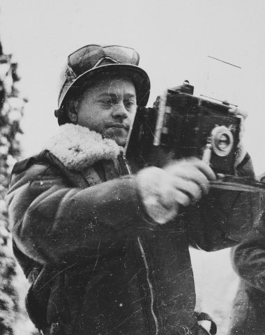 Mickey Rooney poses holding a Signal Photo Company Speed Graphic camera during his visit to the ETO (European Theatre of Operations)..jpg